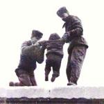 Gardes soulevant un enfant par dessus le mur de Berlin vers 1961
